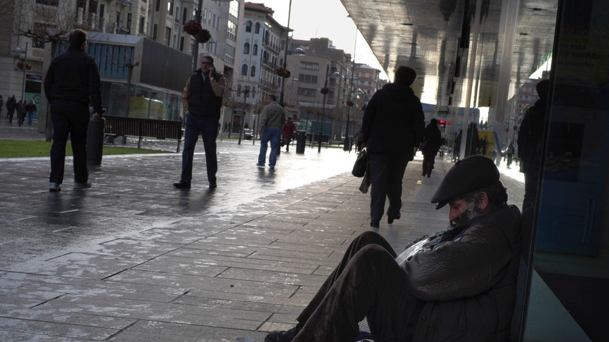 A man begging on the street as people walk past him in Pamplona, northern Spain on Friday, Jan. 3, 2014. The Labor Ministry says the number of people registered as unemployed in Spain fell by 107,570 in December, the best drop on record for the month and welcome news for an economy struggling to emerge from more than two years of recession. Quarterly unemployment surveys, seen as more accurate by economists, show that Spain's unemployment rate was 26 percent in the third quarter, with 6 million people jobless. The rate is the second highest in the 28-country European Union after Greece. (AP Photo/Alvaro Barrientos)