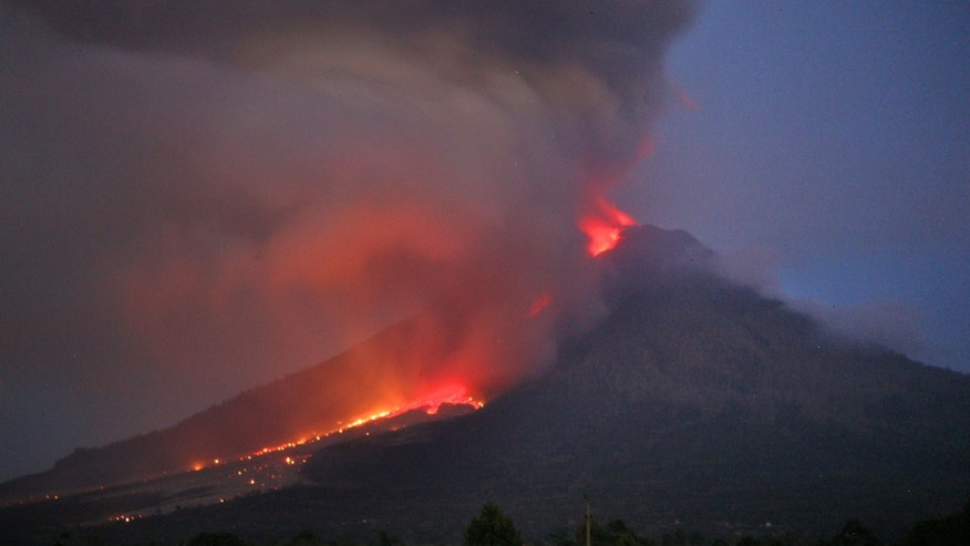 Mount Sinabung spews lava and volcanic ash as seen from Tiga Kicat, North Sumatra, Indonesia, early Tuesday, Jan. 7, 2014. The volcano has sporadically erupted since September, forcing thousands of people who live around it slopes to flee to safer areas. (AP Photo/Binsar Bakkara)