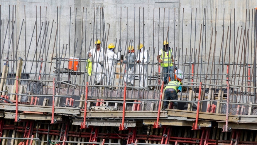 Construction workers labor at the site of the Panama Canal's Pacific expansion project in Cococli, on the outskirts of Panama City, Saturday, Jan. 4, 2014. The consortium responsible for most of the canal expansion issued an ultimatum giving the Panama Canal Authority under a month to pay for a cost overrun to build a third set of locks, threatening to halt the Panama Canal's expansion. (AP Photo/Arnulfo Franco)