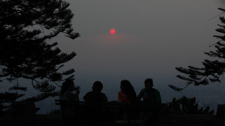 A group of people relax on a park bench at Cerro San Cristobal Park overlooking the Chilean capital which is shrouded by a cloud of smoke from dozens of forest fires that burn near Santiago, Chile, Wednesday Jan. 8, 2014. Residents of Santiago have been suffering from high levels of air pollution caused by the fast-spreading forest fires. The blazes that started over the weekend have caused more than $100 million in property losses. (AP Photo / Luis Hidalgo).