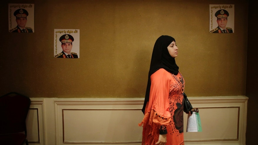 "FILE - In this Monday, Sept. 16, 2013 file photo, an Egyptian woman holds a petition form to nominate Defense Minister Gen. Abdel-Fattah el-Sissi to run for president while listening to a talk in a campaign at a hotel in Cairo, Egypt. Posters of Defense Minister el-Sissi are taped on the wall. The Arabic on the posters reads, ""God bless you, Sissi,"" and ""Army, police and all Egyptians, One arm."" Egypt's military chief is looking for a strong turnout in next week's nationwide constitutional referendum as a mandate on whether he should run for president, senior officials tell the AP. The popular general who ousted President Mohammed Morsi and ordered a crackdown on the Muslim Brotherhood could be disappointed as his Islamist foes have promised a boycott and mass demonstrations raising fears of violence that are likely to keep voters at home. (AP Photo/Hiro Komae, File)"
