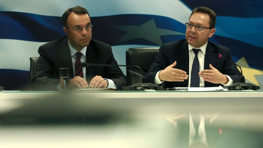 Greek Finance Minister Yiannis Stournaras, right, speaks next to Deputy Finance Minister Christos Staikouras during a press conference about Greece's EU presidency in Athens, on Tuesday, Jan. 7, 2014. Greek authorities have imposed an 18-hour ban on protests across the center of Athens during events planned Wednesday to mark the inauguration of the nation's six-month presidency of the European Union.(AP Photo/Petros Giannakouris)
