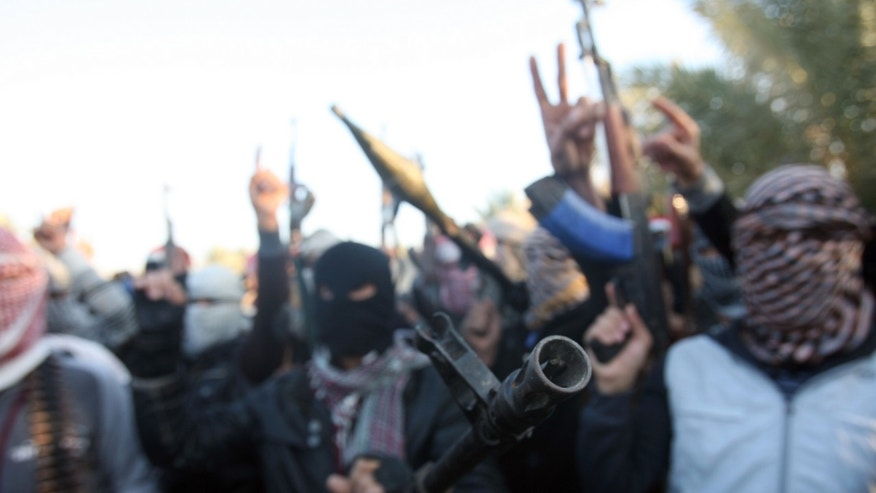 Gunmen gather in a street as they chant slogans against Iraq's Shiite-led government and demanding that the Iraqi army not try to enter the city in Fallujah, 40 miles (65 kilometers) west of Baghdad, Iraq, Tuesday, Jan. 7, 2014. Fierce clashes erupted Tuesday between Iraqi special forces and al-Qaida-linked militants outside the city of Fallujah, a flare-up in a days-long standoff in the Sunni-dominated western province of Anbar, Iraqi officials said. (AP Photo)
