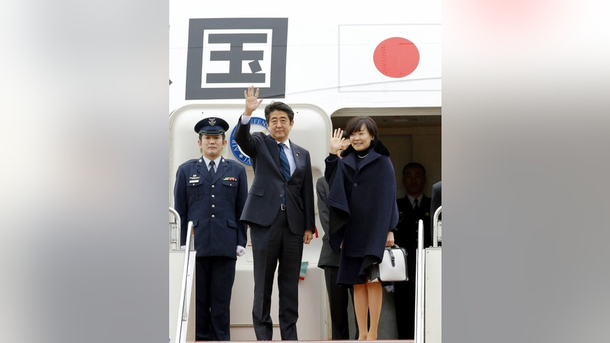Japanese Prime Minister Shinzo Abe, center, and his wife Akie wave as they depart for Africa, at Haneda Airport in Tokyo Thursday, Jan. 9, 2014. Abe is heading to Africa, keeping up a busy overseas travel schedule designed to boost Japan's global profile in the face of China's rise. (AP Photo/Kyodo News) JAPAN OUT, MANDATORY CREDIT