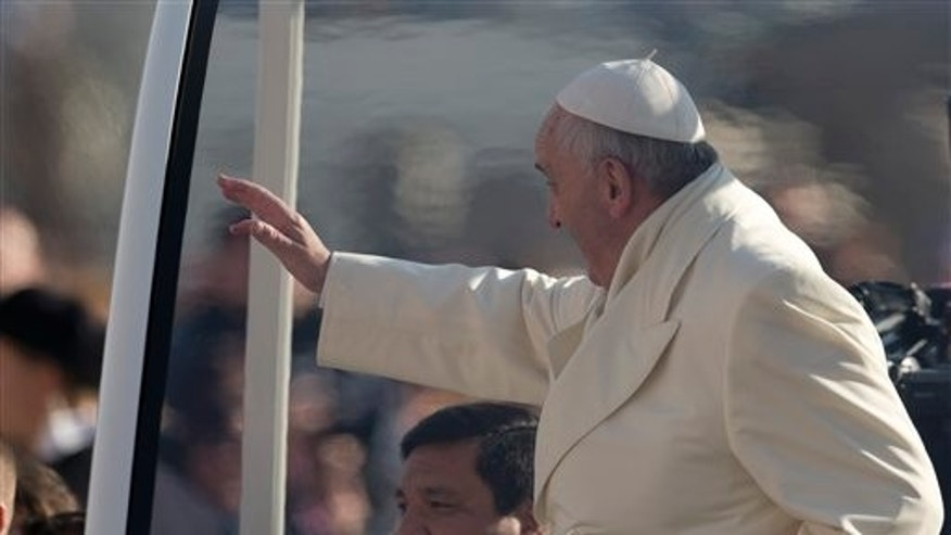 Rev. Fabian Baez sits behind Pope Francis on his popemobile, Wednesday, Jan. 8, 2014.