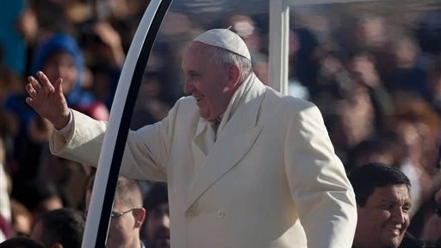 Rev. Fabian Baez sits behind Pope Francis on his popemobile Wednesday, Jan. 8, 2014.