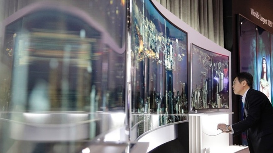 A show attendee looks at LG's 105-inch curved ultra HD TV at the International Consumer Electronics Show(CES) on Tuesday, Jan. 7, 2014, in Las Vegas. (AP Photo/Jae C. Hong)