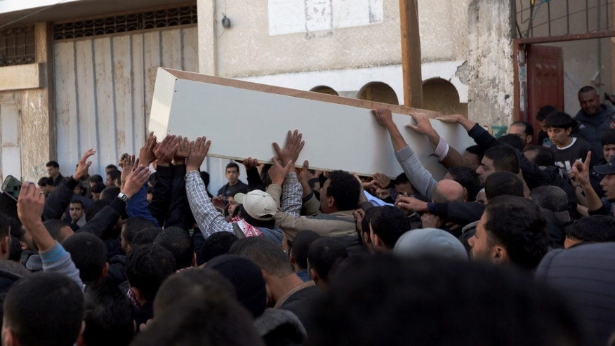 Palestinians carry the body of Mohammed al-Ejlla, 33, during his funeral in Gaza City, Wednesday, Jan. 8, 2014. Al-Ejlla was killed in an explosion in the Gaza Strip on Wednesday, a health official said, prompting an Islamic group to threaten attacks against Israel. The Israeli military said it was not aware of any incident and denied responsibility. (AP Photo/Hatem Moussa)