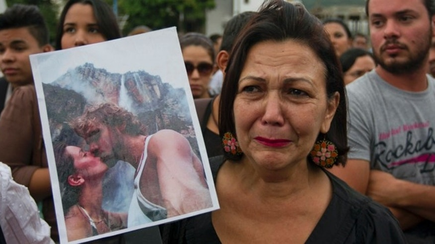 CORRECTS TO EX-HUSBAND - A woman holds up a picture of slain former Miss Venezuela Monica Spear and her ex-husband Henry Thomas Berry during a protest against violence in Caracas, Venezuela, Wednesday, Jan. 8, 2014. Venezuelan authorities say that Spear and her ex-husband were shot and killed resisting a robbery after their car broke down late Monday, Jan. 6, 2014 near Puerto Cabello, Venezuela's main port. (AP Photo/Alejandro Cegarra)