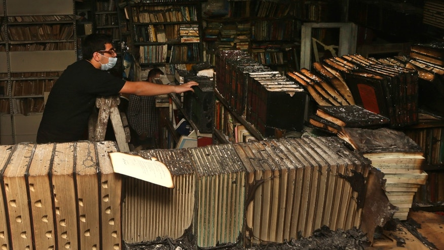 In this picture taken on Sunday, Jan. 5, 2014, a Lebanese activist removes burned books, at the Saeh (Tourist) Library which was set on fire by masked men, in the northern city of Tripoli, Lebanon. Books that were burnt in an arson attack targeting a crammed, chaotic and popular library in the northern Lebanese city of Tripoli have become the latest victim of the country's rising sectarian tensions. (AP Photo/Hussein Malla)