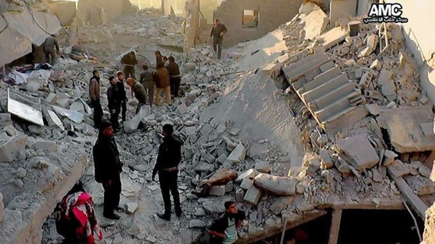 January 6, 2014: In this citizen journalism image provided by Aleppo Media Center, AMC, which has been authenticated based on its contents and other AP reporting, Syrians inspect the rubble of destroyed buildings following a Syrian government airstrike in Aleppo, Syria. (AP Photo/Aleppo Media Center AMC)