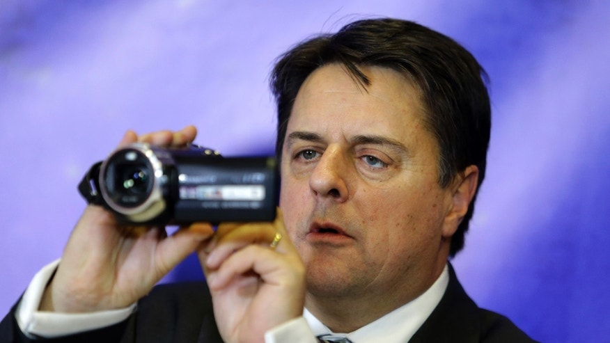 Leader of the far-right British National Party Nick Griffin uses his camera during a news conference in Athens on Friday, Jan. 10. 2014. Griffin, a member of the European Parliament, was in Athens to support Greece's extreme right Golden Dawn Party which is planning to challenge European Court of Human Rights against the recent arrest of the party's leadership on changes of criminal activity. (AP Photo/Thanassis Stavrakis)