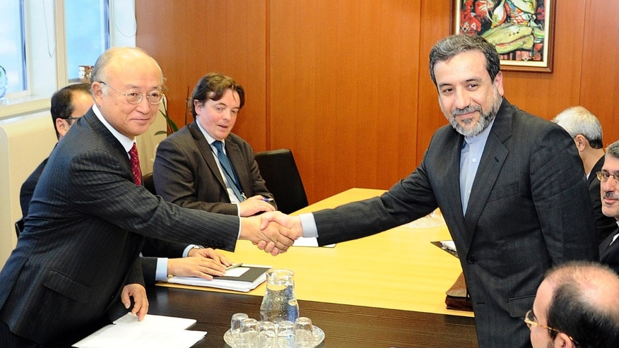 Oct. 28, 2013 - FILE photo of Iran's deputy Foreign Minister Abbas Araghchi, right,  shaking hands with Director General of the International Atomic Energy Agency, IAEA, Yukiya Amano at the International Center in Vienna, Austria. Nearly 7 weeks after signing a landmark nuclear deal, representatives of Iran and 6 world powers hope to reach agreement this week on its implementation.