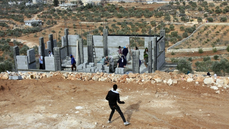 "Palestinians throw stones at Israeli settlers who are later detained by Palestinian villagers in a building under construction near the West Bank village of Qusra, southeast of the city of Nablus, Tuesday, Jan. 7, 2014. Palestinians held more than a dozen Israeli settlers for about two hours Tuesday in retaliation for the latest in a string of settler attacks on villages in the area, witnesses said. The military said the chain of events apparently began after Israeli authorities removed an illegally built structure in Esh Kodesh, a rogue Israeli settlement in the area. In recent years, militant settlers have often responded to any attempts by the Israeli military to remove parts of dozens of rogue settlements, or outposts, by attacking Palestinians and their property. The tactic, begun in 2008, is known as ""price tag."" (AP Photo/Nasser Ishtayeh)"