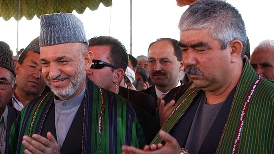 Sept. 26, 2004 file photo, Afghan President Hamid Karzai, left, accompanied by the presidential candidate and regional commander General Abdul Rashid Dostum applaud during his visit to Shiberghan, about 400 kilometers (250 miles) northwest of the capital Kabul.