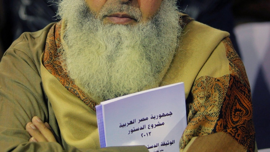 "In this Thursday, Jan. 9, 2014 photo, an Egyptian Salafi holds a copy of the new constitution as he attends a conference to hear a lecture entitled ""Know Your Constitution,"" ahead of a two-day vote on a draft amendment  in El-Saf village, 50 kilometers (31 miles) south of Cairo, Egypt. Arabic reads, ""the constitution of the Arab Republic of Egypt."" The conference, held to rally ""yes"" votes for the charter, highlights a striking alliance that has emerged since the military toppled Islamist President Mohammed Morsi and his democratically elected government last summer. Both the military-backed authorities and the Al-Nour party appear to be benefiting from it, despite the awkwardness. (AP Photo/Amr Nabil)"