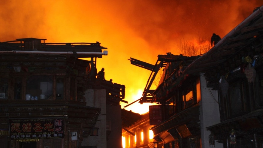 Firefighters work on roofs of buildings while a fire ravages ancient Dukezong town in Shangri-la county, in southwestern China's Yunnan province, Saturday, Jan. 11, 2014. The 10-hour inferno has razed the ancient Tibetan town in the province that's popular with tourists. (AP Photo) CHINA OUT