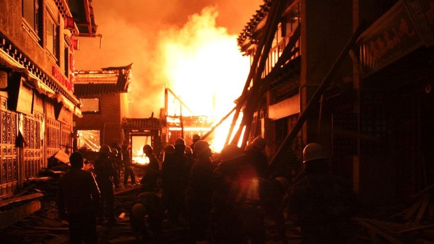 Firefighters fortify a wooden building while a fire ravages ancient Dukezong town in Shangri-la county, in southwestern China's Yunnan province, Saturday Jan. 11, 2014. The 10-hour inferno has razed the ancient Tibetan town in the province that's popular with tourists. (AP Photo) CHINA OUT