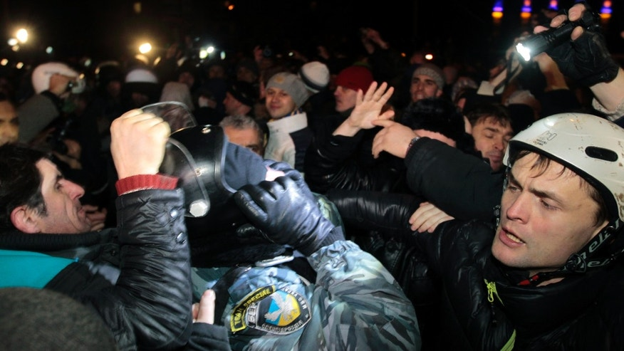 Pro-European Union activists try to remove a helmet from a riot police officer near a Svyatoshin police station in Kiev, Ukraine, Saturday, Jan. 11, 2014. Kiev has been the scene of massive pro-European protests for more than a month, triggered by Ukrainian President Viktor Yanukovych's decision to ditch a key deal with the European Union in favor of building stronger ties with Russia. (AP Photo/Sergei Chuzavkov)