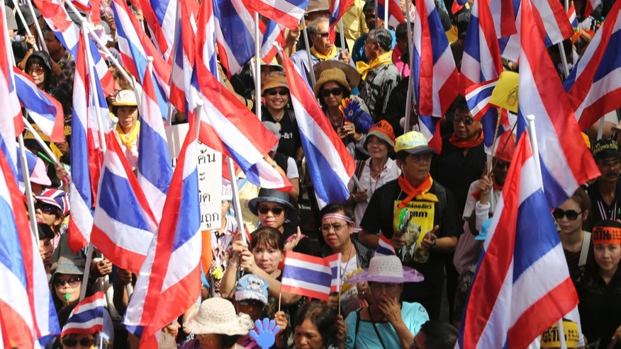 In this Nov. 7, 2013 photo, anti-government protesters wave Thai national flags and march on a street during a rally in Bangkok, Thailand. Anti-government protesters are planning to shut down Thailand's capital on Monday, Jan. 13, 2014 by blocking traffic at key intersections, providing a fitting metaphor for the country's politics: no way forward, no backing out. (AP Photo/Apichart Weerawong)
