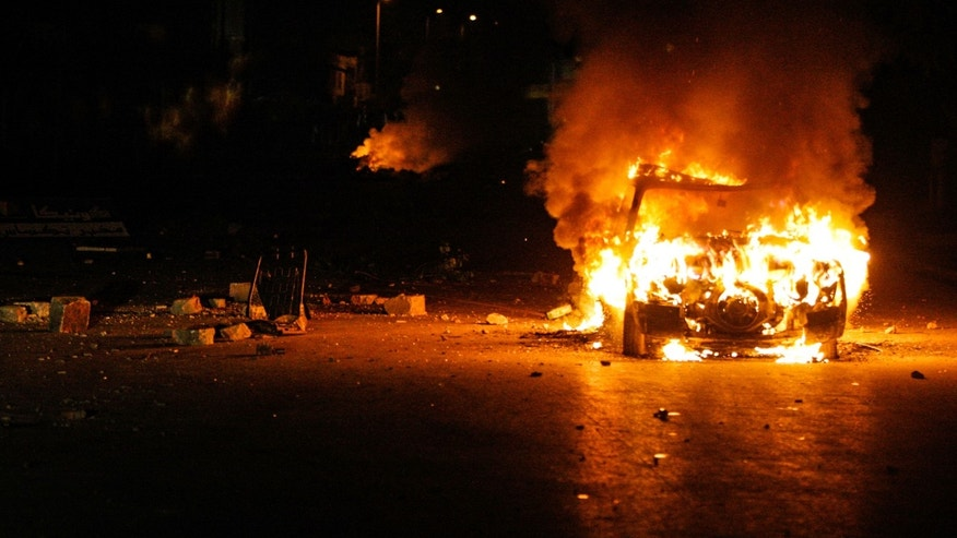 A car burns during clashes with riot police close to a taxi office in Ettadhamen, Tunisia, 5 kms (3 miles) from Tunis, Friday, Jan. 10, 2014.  Clashes erupted in Ettadhamen, near Tunis late Friday evening between police and demonstrators as discontent mounts over new taxes levied by the government late Friday. (AP/Aimen Zine)