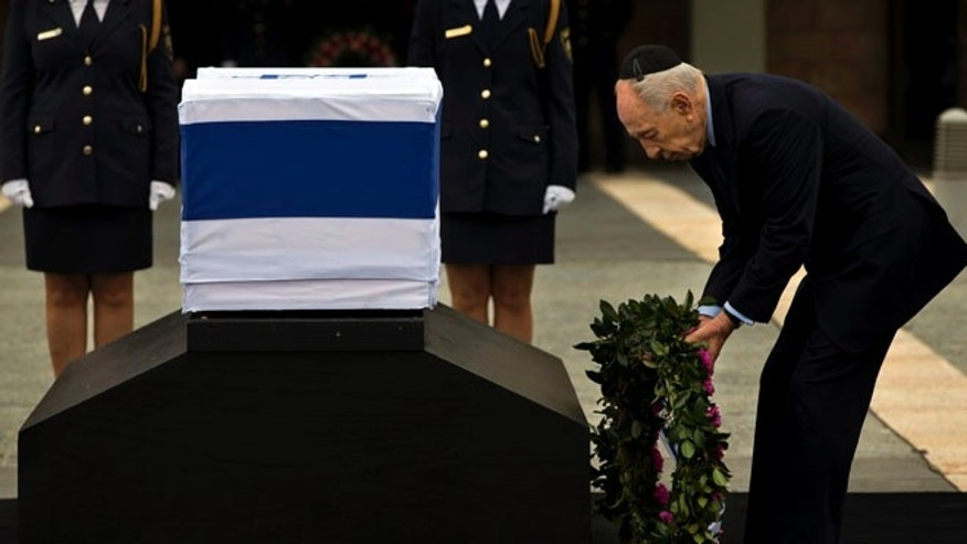 Jan. 12, 2014: Israel's President Shimon Peres lays a wreath next the coffin of late Israeli Prime Minister Ariel Sharon at the Knesset Plaza, Israeli Parliament, in Jerusalem, Sunday.