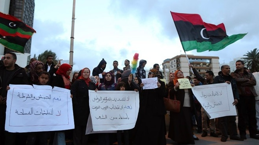 December 27, 2013: In Benghazi, people hold signs during a demonstration against what the protesters said was the decision of the National Congress to extend the period of their stay in power. The temporary government recently passed legislation that make Sharia Law the dominate governing body.