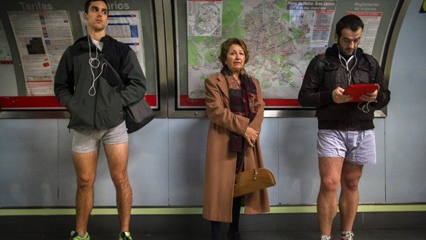 "Jan. 12, 2014: A passenger stands in between participants as they wait for the train without their pants during the 5th annual ""No Pants Subway Ride"" in Madrid, Spain."