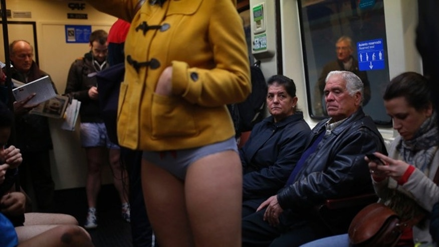 "Jan. 12, 2014: A man looks at a participant who stands on the train without her pants during the 5th annual ""No Pants Subway Ride"" in Madrid, Spain."