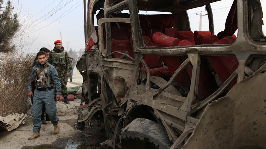 Afghan military forces inspect a suicide attack on a road in Kabul, Afghanistan, Sunday, Jan. 12, 2014. A suicide attacker struck a bus carrying police recruits in eastern Kabul Sunday, wounding several police. (AP Photo/Rahmat Gul)