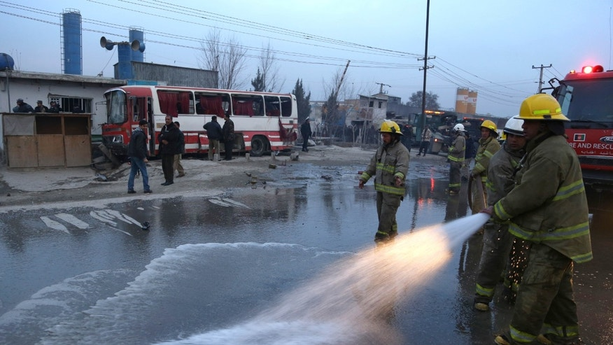 Afghan firefighters wash the street at the site of a suicide attack on a road in Kabul, Afghanistan, Sunday, Jan. 12, 2014. A suicide attacker struck a bus carrying police recruits in eastern Kabul Sunday, wounding several police. (AP Photo/Rahmat Gul)