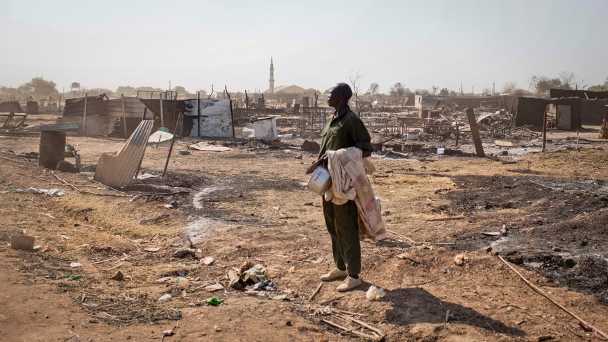 A man carrying his belongings stands amongst the remains of buildings destroyed by the recent fighting, after government forces on Friday retook from rebel forces the provincial capital of Bentiu, in Unity State, South Sudan Sunday, Jan 12, 2014. On Sunday senior South Sudanese government officers inspected the recaptured town of Bentiu, in northern Unity State, that was the scene of intense fighting between government and rebel forces, while a South Sudanese government official claimed rebels had badly damaged petroleum facilities in the state. (AP Photo/Mackenzie Knowles-Coursin)