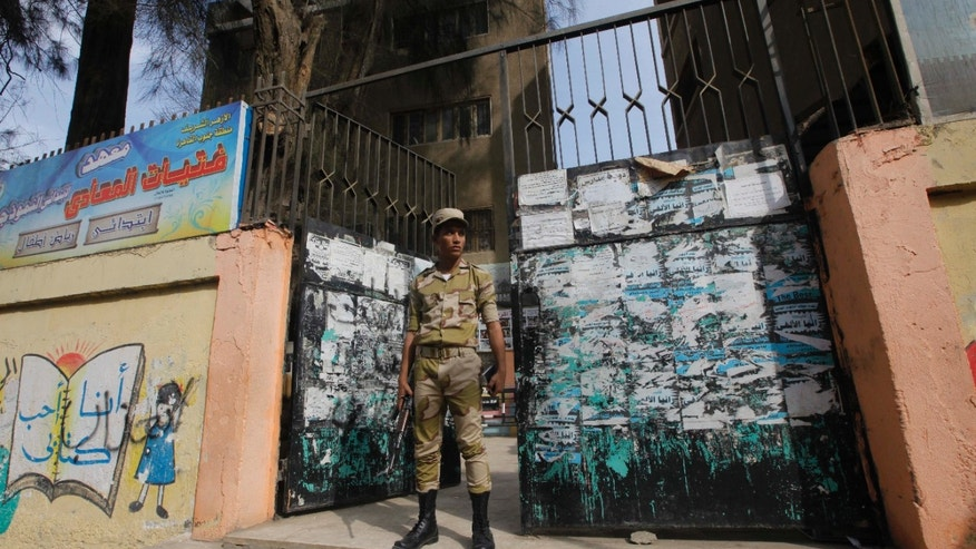 "An Egyptian army soldier stands guard in front of a polling station in Cairo, Egypt, Monday, Jan. 13, 2014. The January 14-15 vote on the draft constitution will be the first real test of the post-Morsi regime. A comfortable ""yes"" vote and a respectable turnout would be seen as bestowing legitimacy, while undermining the Islamists' argument that Morsi remains the nation's elected president. (AP Photo/Amr Nabil)"