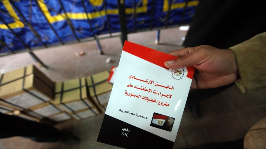 "An Egyptian election worker displays a guide book for voting in the country's constitutional referendum, at the Giza courthouse, in Cairo, Egypt, Monday, Jan. 13, 2014. The January 14-15 vote on the draft constitution will be the first real test of the post-Morsi regime. A comfortable ""yes"" vote and a respectable turnout would be seen as bestowing legitimacy, while undermining the Islamists' argument that Morsi remains the nation's elected president. Arabic reads, ""A guide for voting on the draft amendments of the constitution.""  (AP Photo/Amr Nabil)"