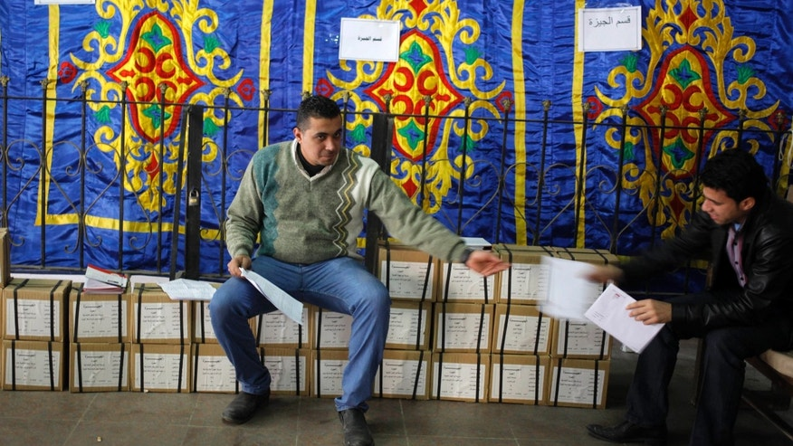 "An Egyptian worker sits on boxes of ballots while receiving a list of polling stations from a colleague, at the Giza courthouse, in Cairo, Egypt, Monday, Jan. 13, 2014. The January 14-15 vote on the draft constitution will be the first real test of the post-Morsi regime. A comfortable ""yes"" vote and a respectable turnout would be seen as bestowing legitimacy, while undermining the Islamists' argument that Morsi remains the nation's elected president. (AP Photo/Amr Nabil)"