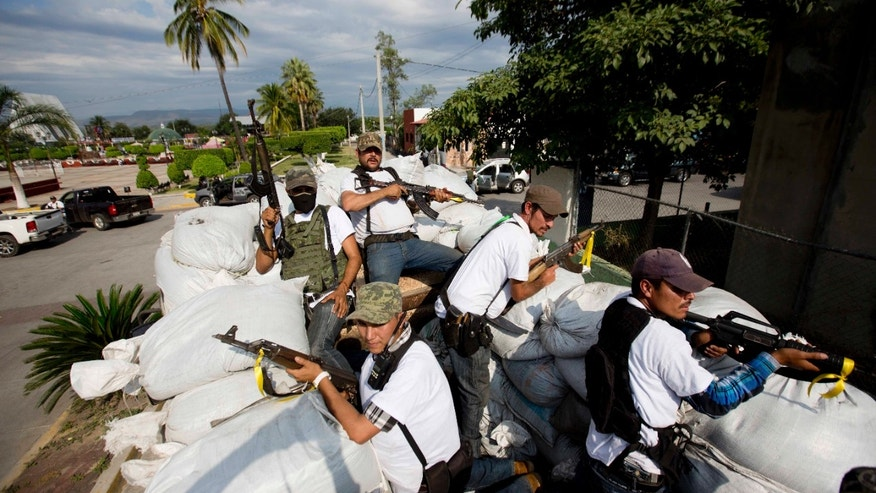 Men belonging to the Self-Defense Council of Michacan, (CAM), ride on a sandbag filled truck while trying to flush out alleged members of the Knights Templar drug cartel from the town of Nueva Italia, Mexico, Sunday Jan. 12, 2014.  The vigilantes say they are liberating territory in the so-called Tierra Caliente and are aiming for the farming hub of Apatzingan, said to be the cartel's central command. Mexican military troops are staying outside the town and there are no federal police in sight. (AP Photo/Eduardo Verdugo)