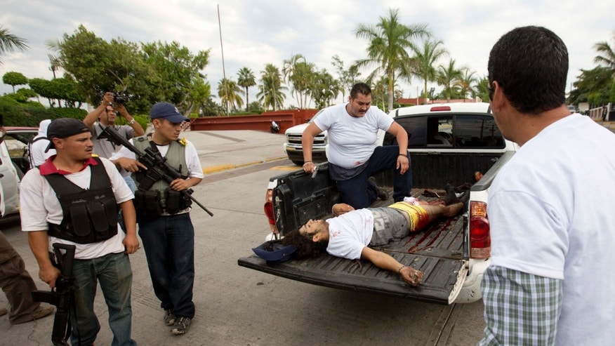 A wounded man belonging to the Self-Defense Council of Michacan, (CAM), is taken away during a firefight while trying to flush out alleged members of the Knights Templar drug cartel from the town of Nueva Italia, Mexico, Sunday Jan. 12, 2014.  The vigilantes say they are liberating territory in the so-called Tierra Caliente and are aiming for the farming hub of Apatzingan, said to be the cartel's central command. Mexican military troops are staying outside the town and there are no federal police in sight. (AP Photo/Eduardo Verdugo)