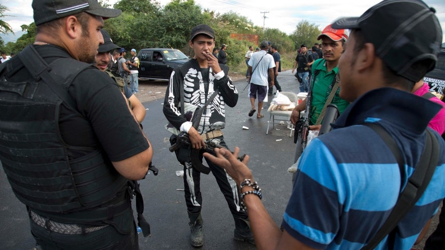 A man belonging to the Self-Defense Council of Michacan, (CAM), dressed in a skeleton costume, stands while organizing as they prepare to move into the larger town of Nueva Italia to flush out alleged members of the Knights Templar drug cartel in the town of Antunez, Mexico, Sunday Jan. 12, 2014.  The vigilantes say they are liberating territory in the so-called Tierra Caliente and are aiming for the farming hub of Apatzingan, said to be the cartel's central command. Mexican military troops are staying outside the town and there are no federal police in sight. (AP Photo/Eduardo Verdugo)