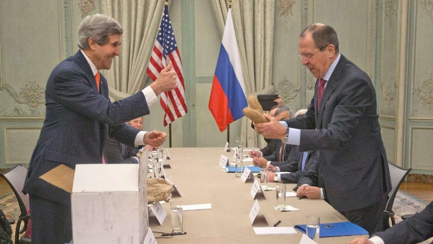 "U.S. Secretary of State John Kerry, standing left, gives a ""thumbs-up"" sign after giving a pair of Idaho potatoes as a gift for Russia's Foreign Minister Sergey Lavrov at the start of their meeting at the U.S. Ambassador's residence in Paris, France, Monday, Jan. 13, 2014. Kerry is in Paris on a two-day meeting on Syria to rally international support for ending the three-year civil war in Syria. (AP Photo/Pablo Martinez Monsivais, Pool)"
