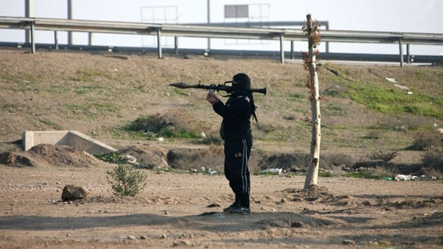 January 12, 2014: A gunman holds his weapon as he stands guard in Fallujah, 40 miles west of Baghdad, Iraq. Iraqi forces have yet to militarily try to reassert control over Fallujah, which remains in the hands of the militants and tribal gunmen opposed to the central government. (AP Photo)