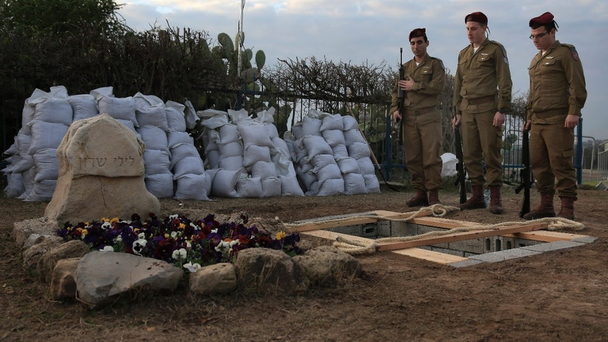 Israeli soldiers from a paratroopers unit rehearse at the grave site for late Israeli Prime Minister Ariel Sharon, who will be buried next to his wife, outside his ranch in Havat Hashikmim, southern Israel, Sunday, Jan. 12, 2014. A state memorial is planned for Monday with the participation of Israeli and world leaders, the prime minister's office said. (AP Photo/Tsafrir Abayov)