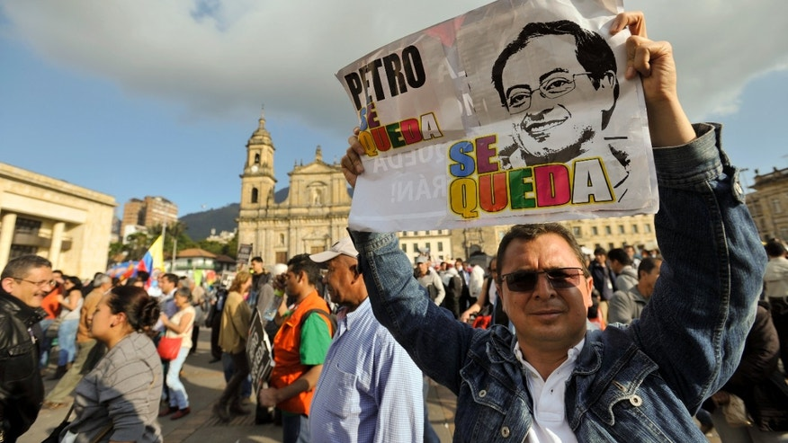 "A supporter of Bogota's Mayor Gustavo Petro holds a sign reading in Spanish; ""Petro Stays"" in front of the city hall in Bogota, Colombia, Monday, Jan. 13, 2014. Colombia's Inspector General Alejandro Ordonez ratified on Monday the impeachment of Petro for the mismanagement of the city's garbage collection system. (AP Photo/Carlos Julio Martinez)"