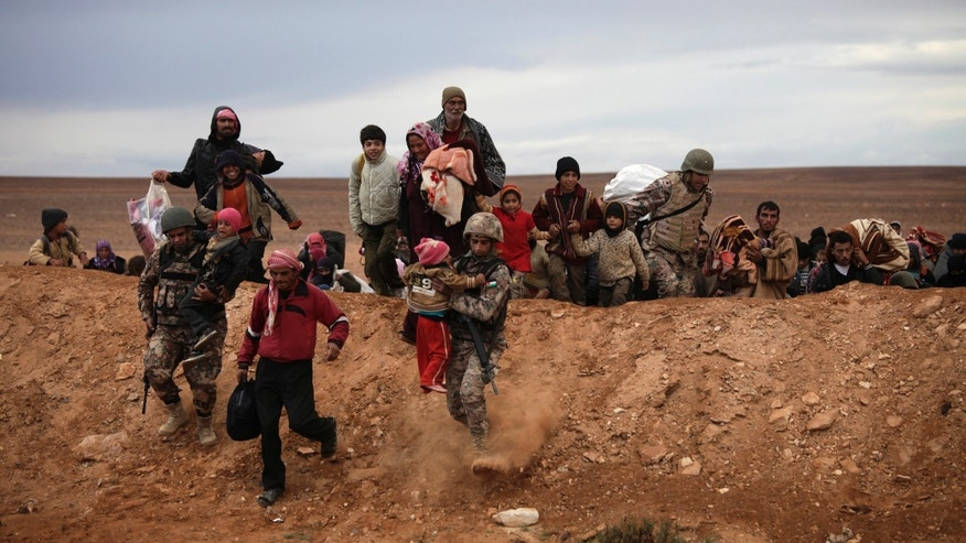 FILE - In this file photo taken Thursday, Dec. 5, 2013, newly-arrived Syrian refugees carry their belongings after crossing into Ruweishid, Jordan. Relief aid officials are hoping wealthy Gulf states and other international donors gathering for a major fundraising drive in Kuwait will step up their giving to help Syrians affected by the country's civil war, warning that conditions are fast deteriorating as refugee numbers grow and prospects for a ceasefire remain elusive. (AP Photo/Mohammad Hannon, File)