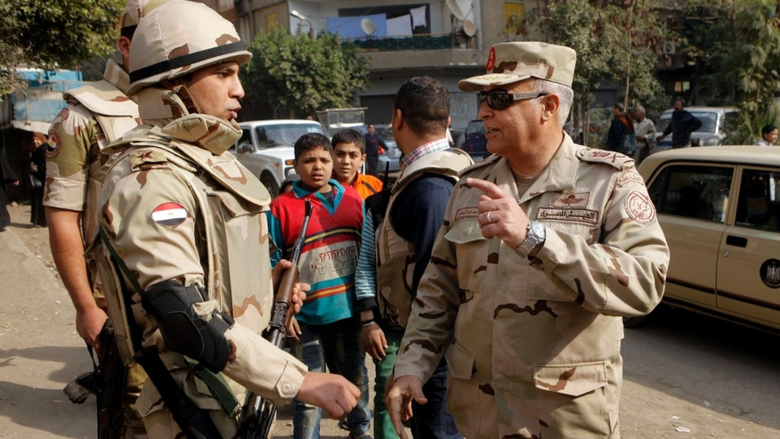 Commander of the Egyptian army Special Forces Medhat el-Nahas, right, speaks to a solider as he visits polling stations in Cairo, Egypt, Tuesday, Jan. 14, 2014. Egyptians have started voting on a draft for their country's new constitution that represents a key milestone in a military-backed roadmap put in place after President Mohammed Morsi was overthrown in a popularly backed coup last July. (AP Photo/Amr Nabil)