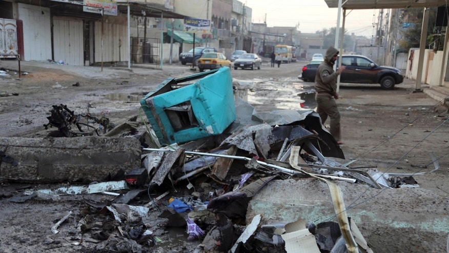 A man inspects the aftermath of car bomb attack in Baghdad, Iraq, Tuesday, Jan. 14, 2014. Fresh violence killed and wounded scores on Monday in Iraq, where the U.N. chief was on a visit urging leaders to tackle the issues driving fighting in a western province where the army is in a standoff with al-Qaida-linked fighters. (AP Photo/Karim Kadim)