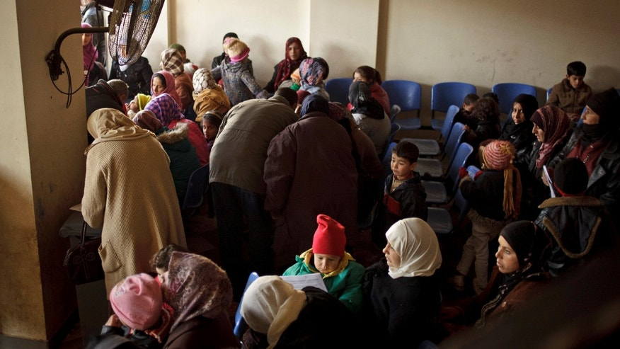 This Wednesday, Dec. 18, 2013 photo shows Syrians waiting for their appointments at the U.N. refugee agency's registration center in Zahleh, in Lebanon's Bekaa Valley. In Lebanon, where Syrian refugees now equal one-third of the population, the problem for many Syrians is made worse by the government's refusal to establish official refugee camps, further complicating aid efforts and leading to a chaotic, fractured operation with major gaps in coordination.(AP Photo/Maya Alleruzzo)