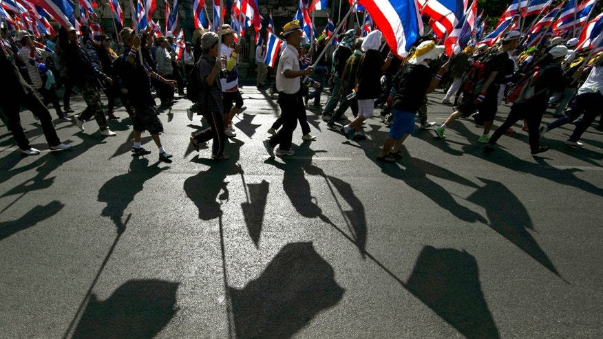 Thai anti-government protesters march with national flags as they head to the office of the National Economic and Social Development Board (NESDB) Tuesday, Jan. 14, 2014, in Bangkok, Thailand. Anti-government protesters who blocked off intersections across Thailand's capital began marching toward several government ministries Tuesday on the second day of a renewed push to derail elections next month and unseat the prime minister. (AP Photo/Wason Wanichakorn)