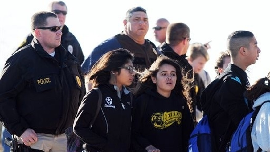 Students surrounded by officials are escorted from Berrendo Middle School after a shooting, on Jan. 14, 2014, in Roswell, N.M.
