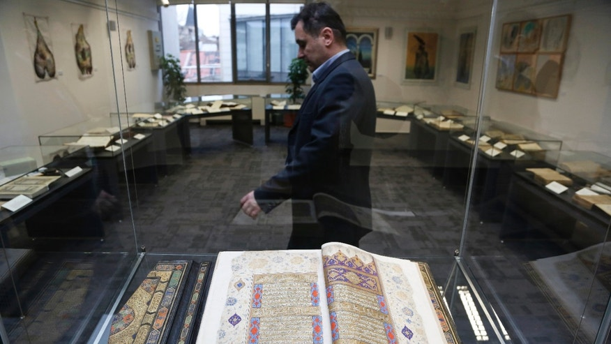 Bosnian security worker passes by old books on display during opening ceremony of Gazi Husrev-bey library in Sarajevo, on Wednesday, Jan. 15, 2014.  Sarajevo reopens the 477-year old library on Wednesday, that contains the biggest collection of oriental books and manuscripts in Southeast Europe, after it was rebuilt with the financial donation from Qatar. Dodging bullets and bombs during the 1992-95 Bosnian war and the city's siege, Sarajevans moved the manuscripts eight times to different locations to save them from destruction. (AP Photo/Amel Emric)