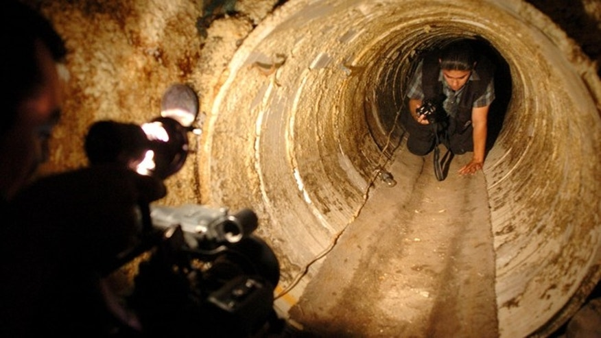 File-This July 8, 2004 file photo shows a Mexican federal agent crawls through a hidden tunnel, presumably used to transport drugs from Mexico to the U.S. The job of searching these networks can be dangerous, so the U.S. Border Patrol is unveiling its latest technology in the underground war, a wireless, camera-equipped robot that can do the job in a fraction of the time. (AP Photo/David Maung)